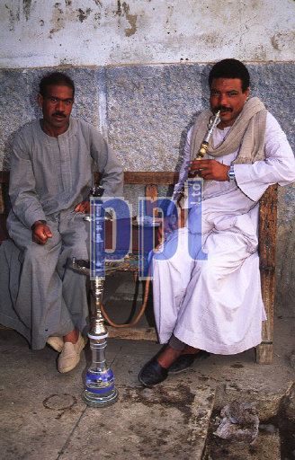 Men in traditional dress smoking blow-pipes Egypt