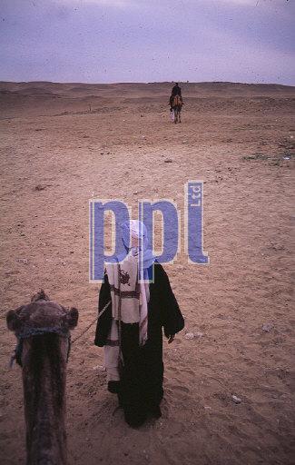Camel & owner in desert at Giza Egypt
